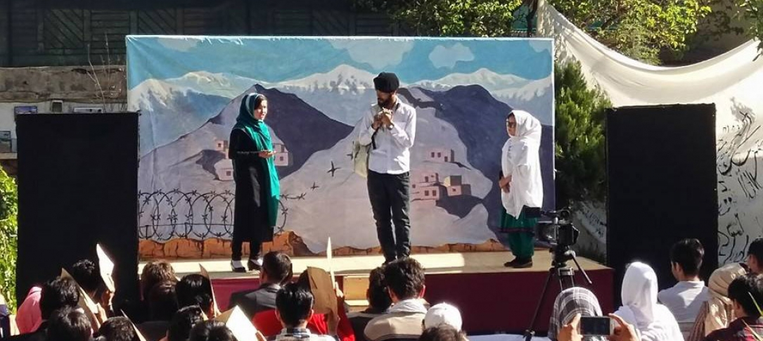 Young Afghans perform a play on an outside stage