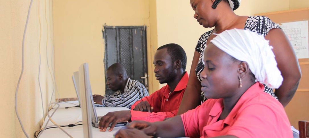 Two men and a woman sit at a table working on laptop computers while another woman stands behind them.