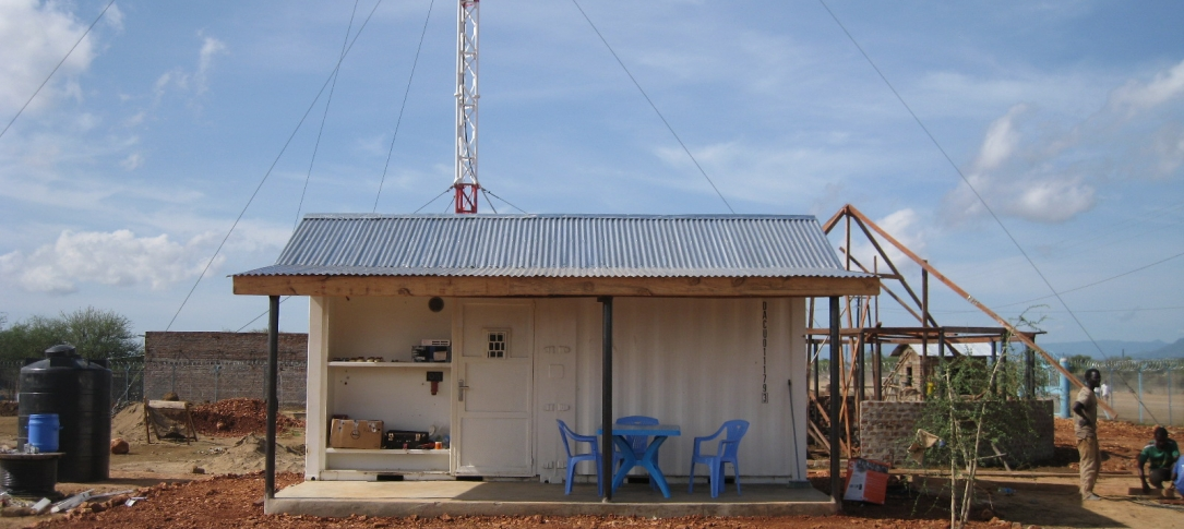 Exterior of a radio station in South Sudan - small white building with solar panels on the roof