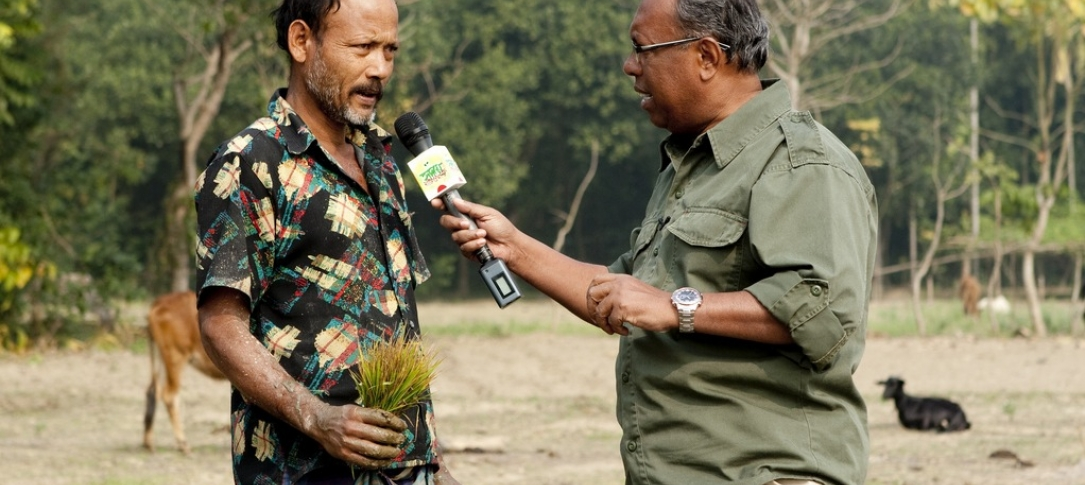 A journalist holds a mic up to a farmer - they are standing in a field