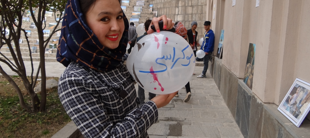 A young woman holds a balloon with some writing on it