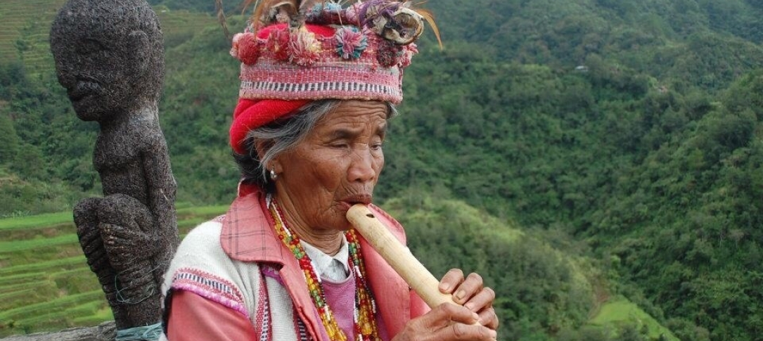 A woman plays a flute in the mountains