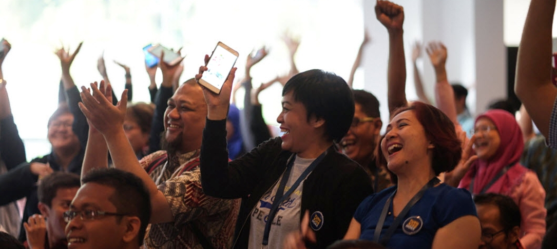 A group of people smile and clap and wave their hands