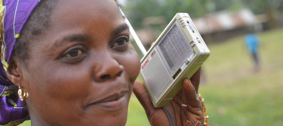 A woman listens to a transistor radio