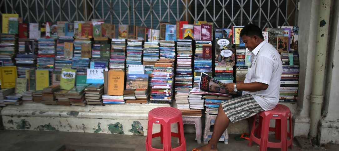 A man sits reading in front of a newstand