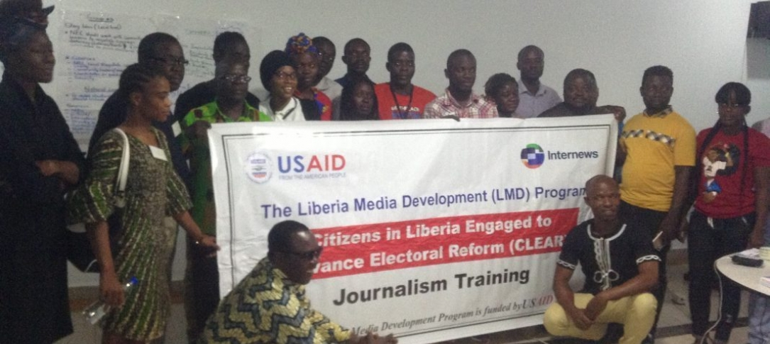 A group of people pose holding a large USAID banner in front of them