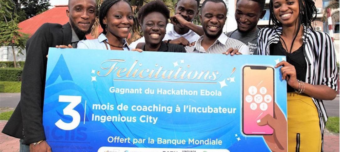 A group of young people hold up a banner about the Ebola hackathon