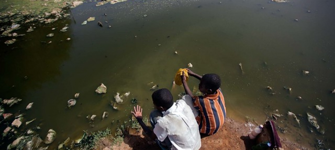 two boys sit by a body of water with garbage in it