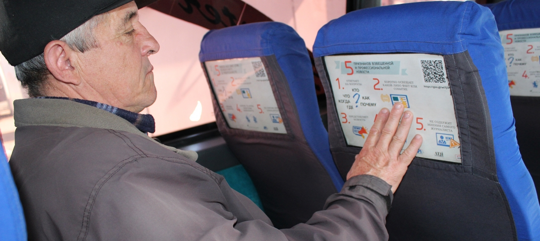 A man sits on a bus and points at a poster attached to the back of the seat in front of him