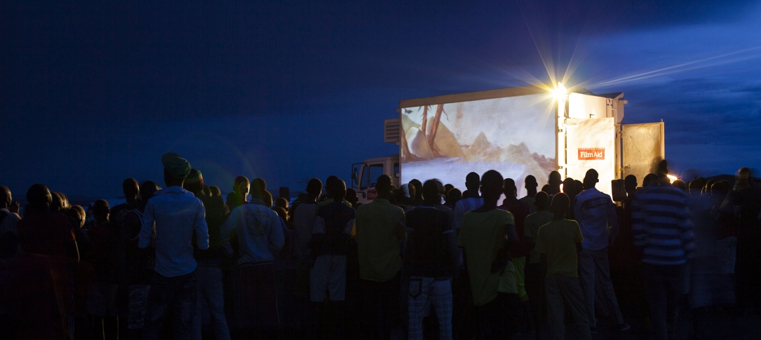A crowd of people watch a movie projected on the side of a truck