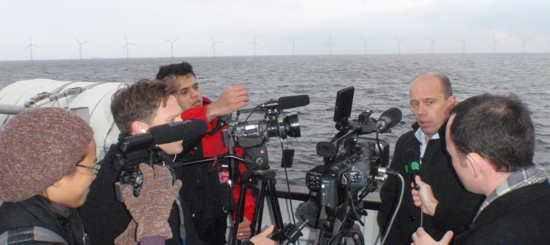 A group of journalists films a man on a boat