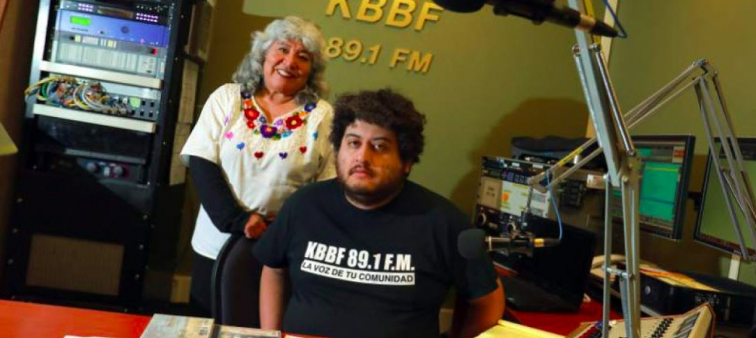 A man sits in a radio studio while a woman stands behind him