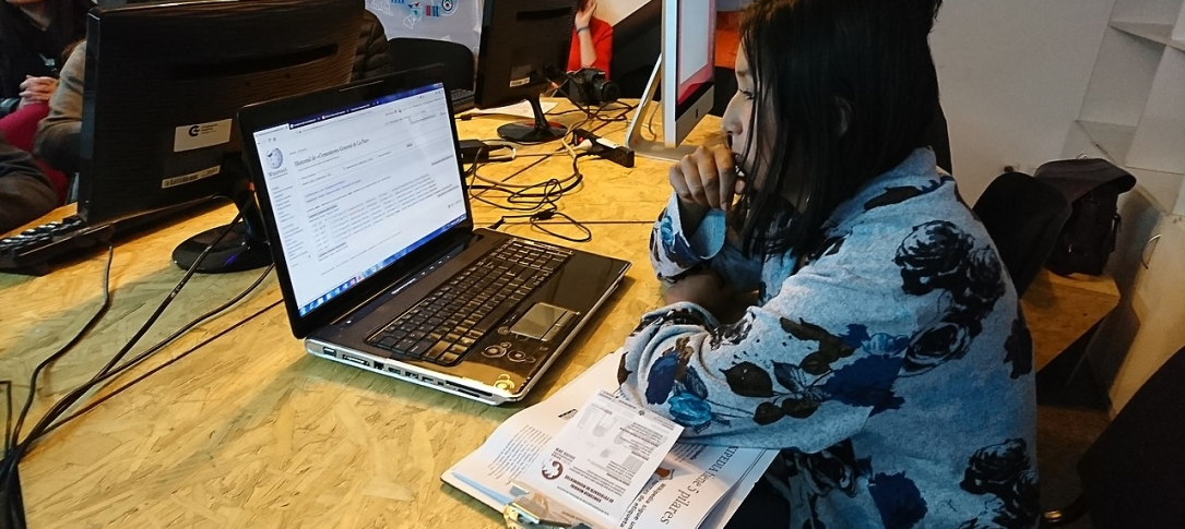 A woman sits in a cafe working on a laptop computer
