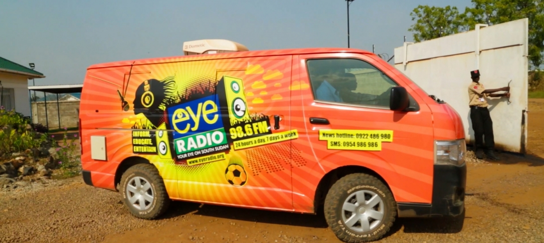 "A van with an ""Eye Radio"" sign on the side stops on a dirt road"