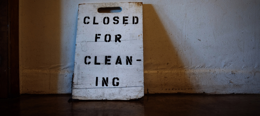 "A sign saying, ""Closed for cleaning"" leans against a wall"