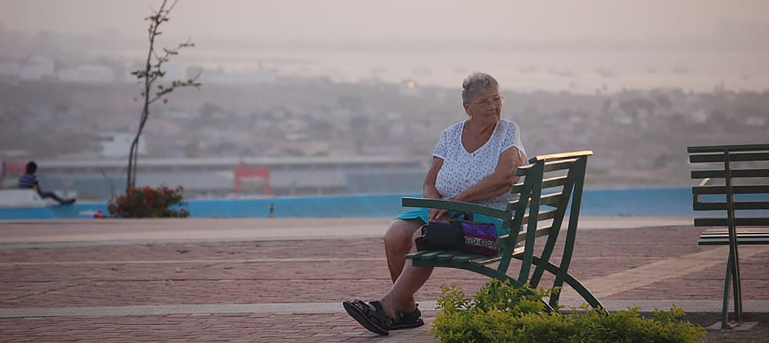An older woman sits on a bench overlooking a city in Ecuador