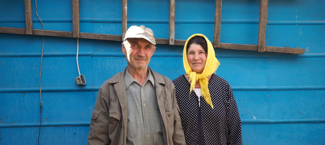 A man and a woman stand outside a building painted blue with a ladder hanging on it