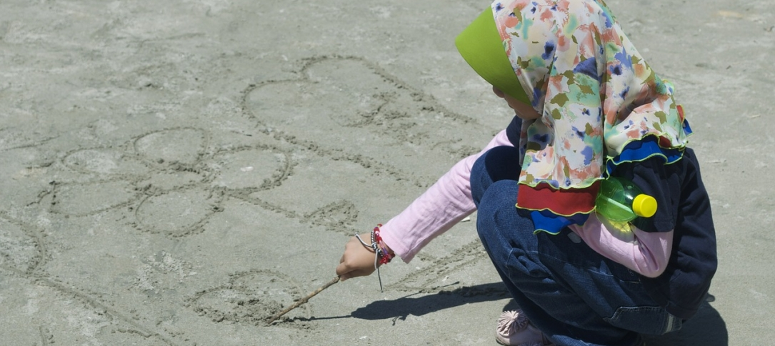 a little girl draws in the sand at the beach