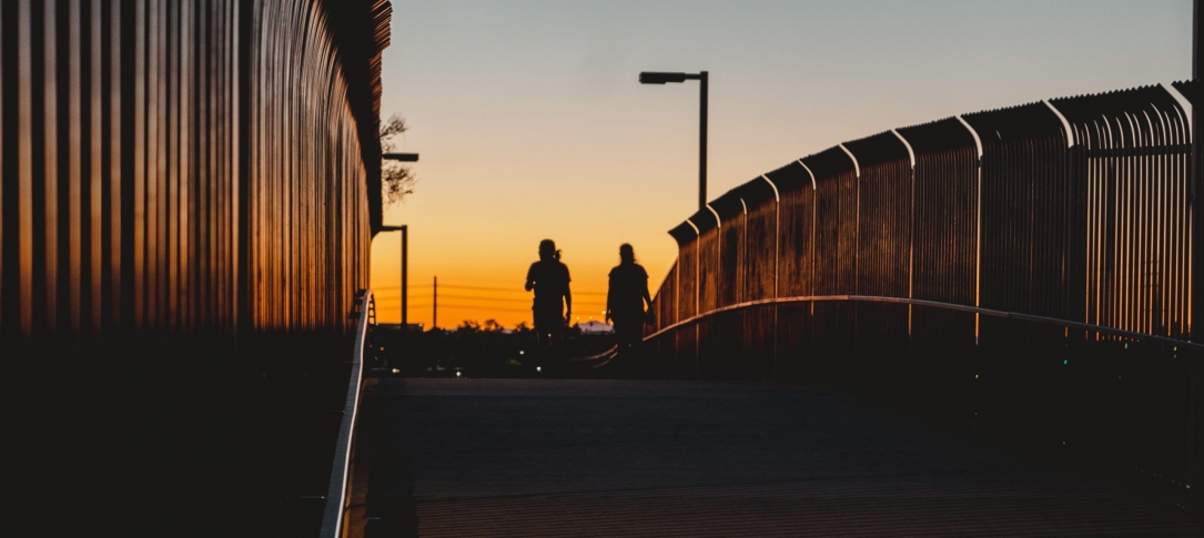 2 people cross a bridge in the sunset