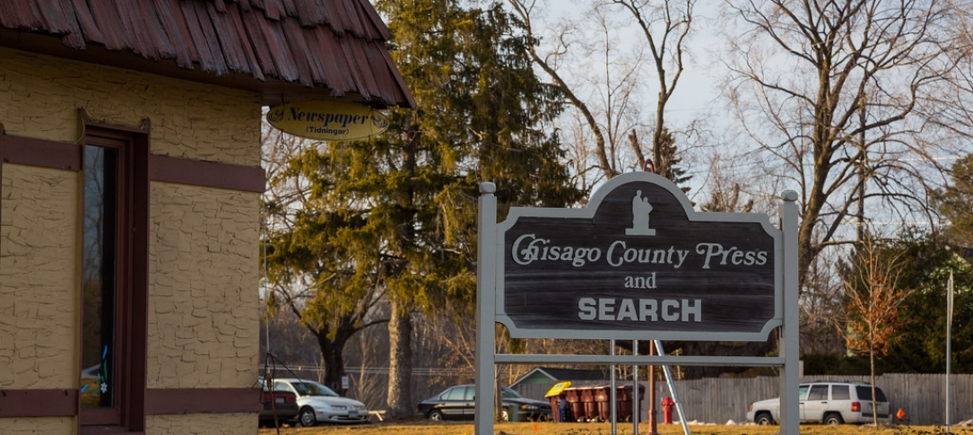 "A sign outside a building says, ""Chisago County Press and Search"""