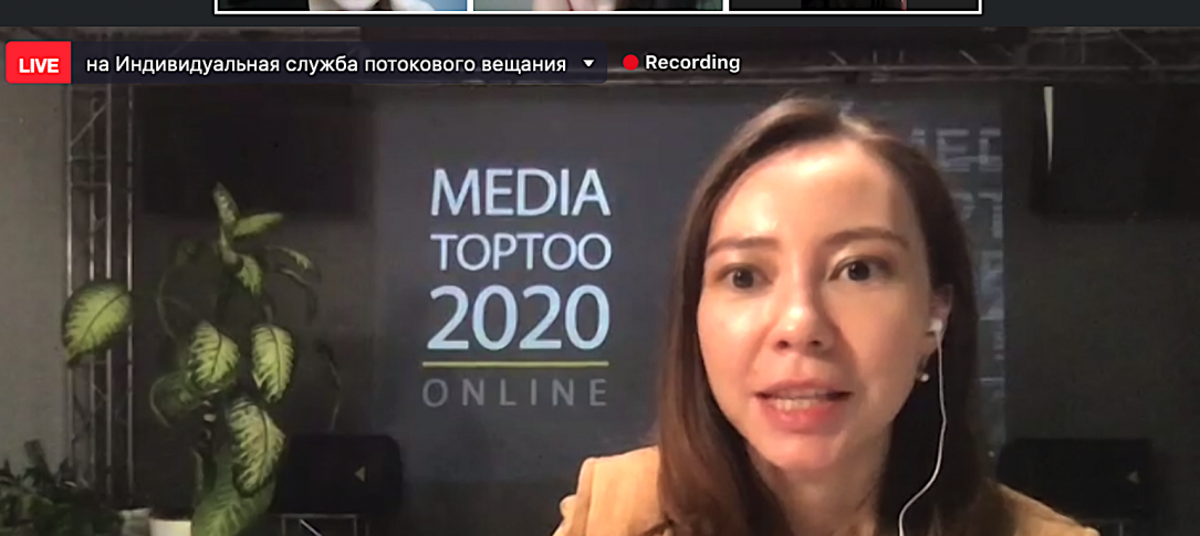"A woman sits - behind her is a screen with multiple images of people and a sign saying ""Media Toptoo2020"""