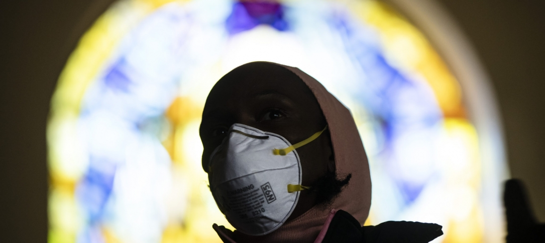 A person wearing a mask with a window behind them