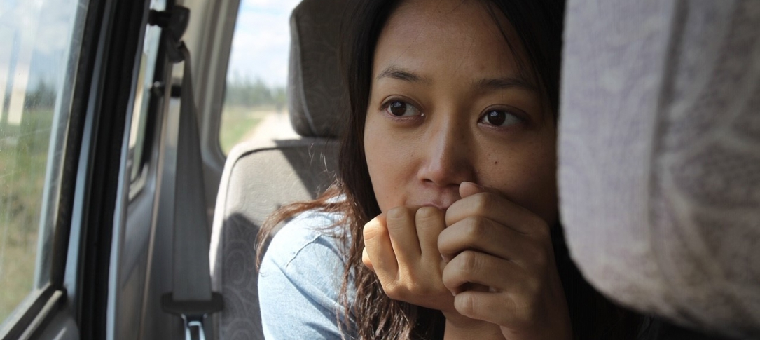 A woman sits in a car - close up of her face