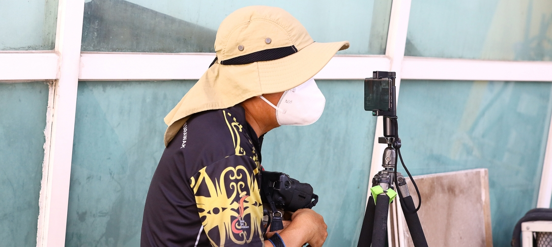 A man wearing a hat and mask looks through a camera mounted on a tripod