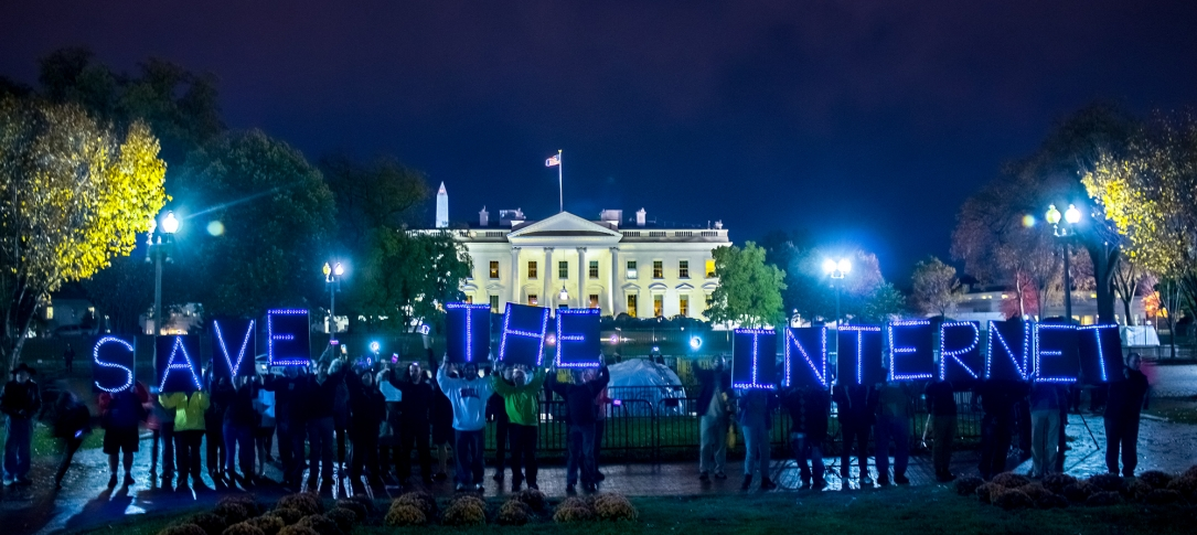 "Protesters stand in front of the White House at night holding posters that spell out ""save the internet"""