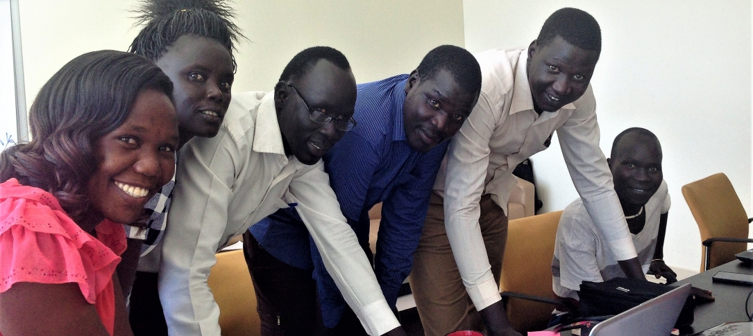 Six South Sudanese journalists line up at their computers.