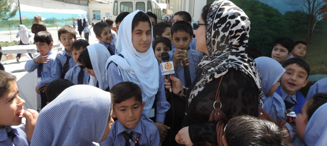 A woman journalist interviews a young woman while other children gather around