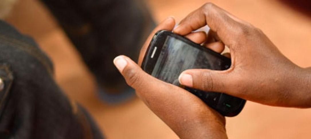 Hand holds a mobile phone (by Meredith Kohut/Internews)