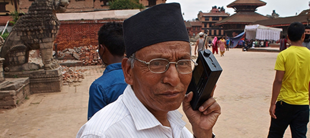 A man in Nepal holds a portable radio to his ear