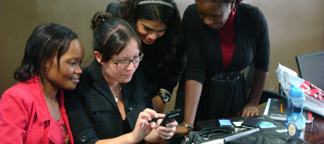 Four women look at a smart phone