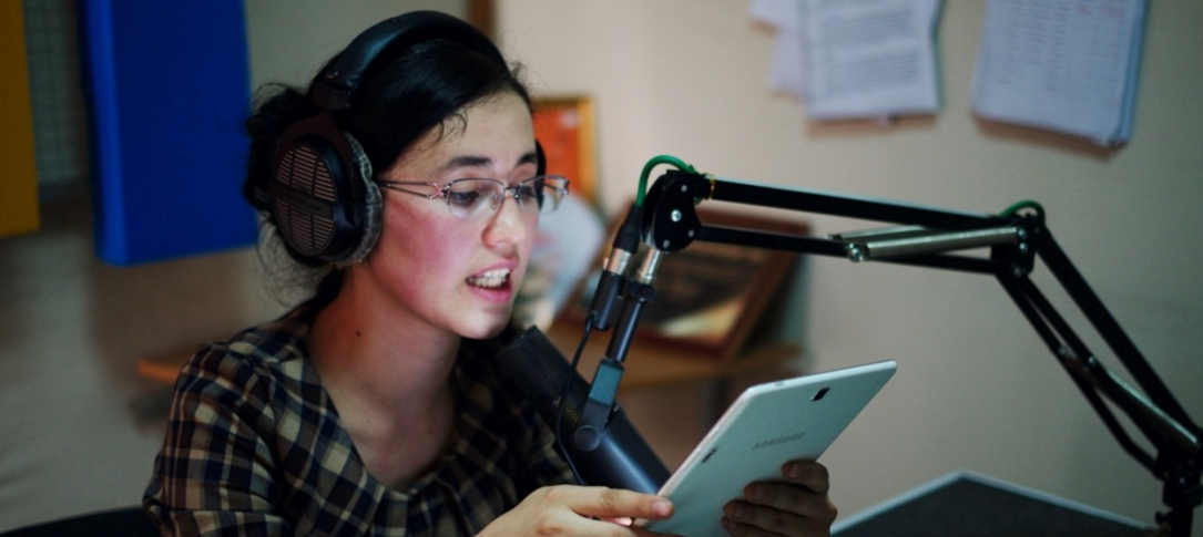 A woman sits at a mic in a radio studio reading from a paper
