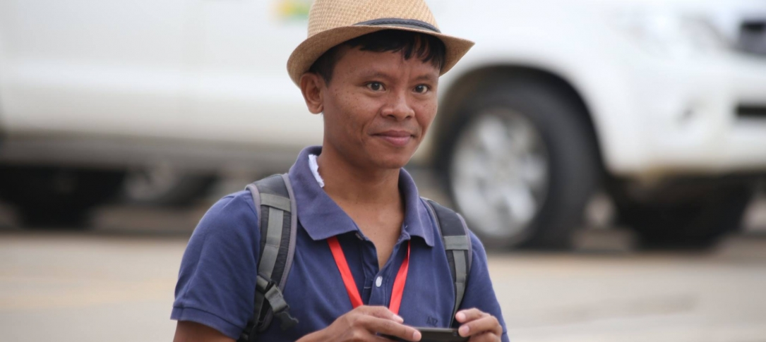 A man holding a smart phone stands by the side of a road. He's wearing a straw hat.