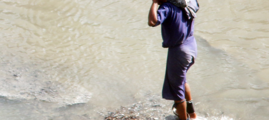A man with his legs shackled carries a rock through the water