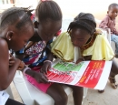 Three girls look at a poster with information about Ebola. A little boy sits behind them.