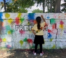 A girl draws on a wall painted with graffiti