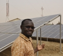 A man stands in front of a bank of solar panels
