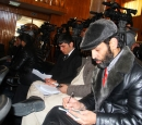 Journalists sit on chairs writing while some stand behind videotaping