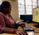 A woman sits at a computer that has an infographic on the screen.