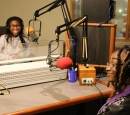 Two African American women, both wearing headphones, face each other in a radio studio.