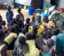 A group of children in an IDP camp listen to a radio outside.