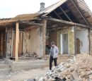A woman walks by a destroyed house.