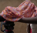 A man looks through a video camera - there is a scarf over his head and the camera.