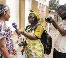 A woman journalist with a mic interviews a woman while a man takes a photograph