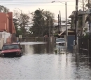 A flooded street with 2 cars half submerged