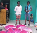 4 women stand by a pile of food sacks outside a house