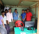A group of people stand in a shack with a computer on a desk